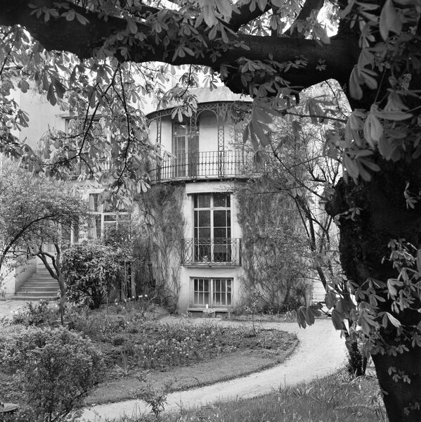 Exterior of the entrance front to a house at Downshire Hill, Hampstead with curving garden path and spring flowers in bloom, and a tree in the foreground to right. Photographed by John Gay. Date range: 1960 - 1965