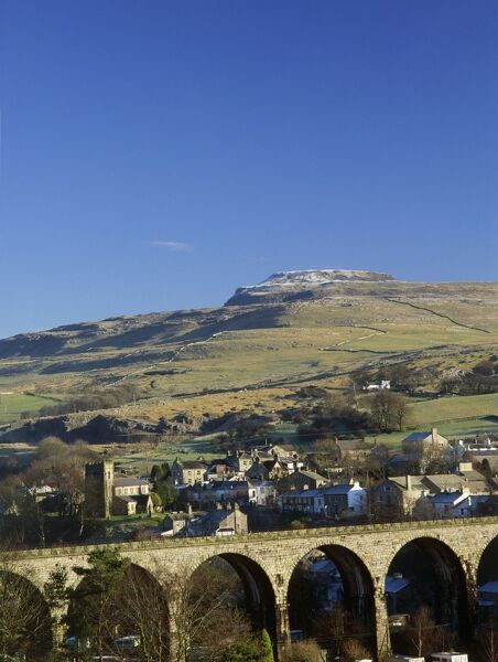 INGLEBOROUGH IRON AGE HILL FORT, Yorkshire Dales. View across to the village of Ingleton, showing the Viaduct and Ingleborough Hill Fort behind