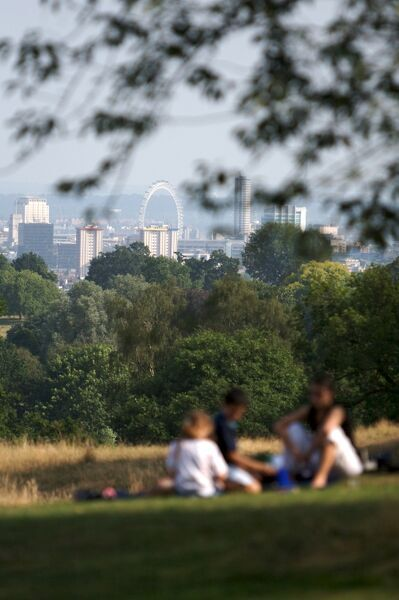 KENWOOD HOUSE, London. The London skyline with a group of visitors picnicking on the lawn in the foreground