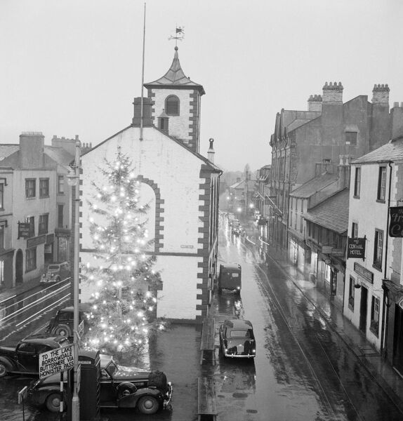MOOT HALL, Main Street, Keswick, Cumbria. A view north west from an elevated position in Main Street, Keswick, looking towards the Moot Hall and showing a large illuminated Christmas tree in the market square, with vehicles leaving trails of light in the dark
