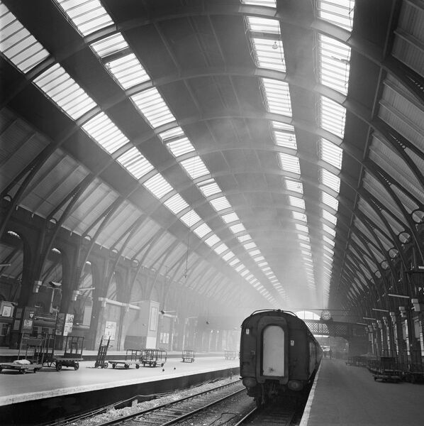 KINGS CROSS STATION, London. Interior view of the train shed at Kings Cross Station showing a train standing beside an almost empty platform. Photographed by John Gay. Date range: 1960-1972