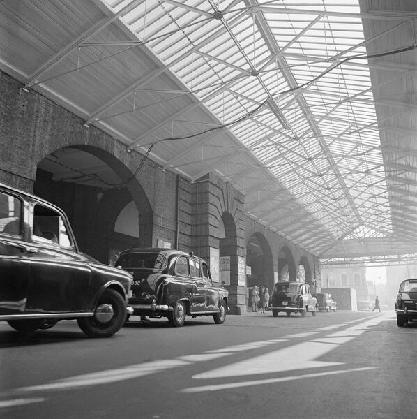KINGS CROSS STATION, Euston Road, London. A line of taxis (black cabs) waiting under the canopy at Kings Cross Station. Date range:1960 - 1972. John Gay
