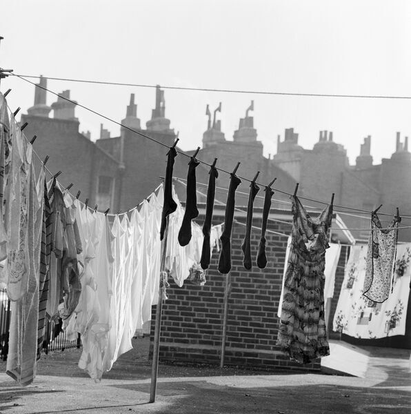 Lines of washing drying in the sun with the outlines of roofs and chimney pots behind, in either Islington or Camden. Photographed by John Gay. Date range: 1960 - 1965