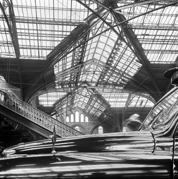 LIVERPOOL STREET STATION, London. Interior view looking across the bonnet of a taxi and showing roof structure within Liverpool Street Station. Photographed by John Gay. Date range: 1960-1972