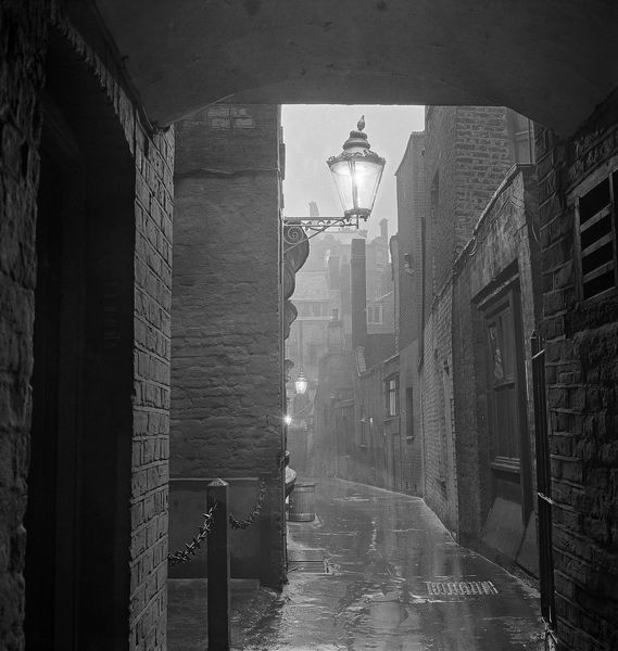 Rainy view of a dimly lamp lit alley in London's theatre land off St Martin's Lane. Photographed by John Gay, early 1960s