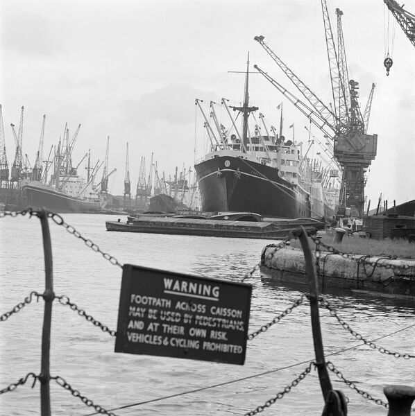 LONDON DOCKS. Ships and barges moored at the docks with cranes overhead, a warning sign hanging on chains in the foreground. Photographed by John Gay in July 1965