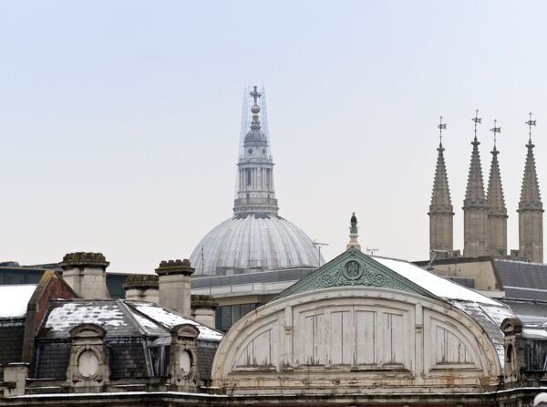Smithfield Market, City of London. Skyline with the rooves of the market buildings, the dome of St Pauls Cathedral and the Shard appearing behind the dome. There is snow on the roofs