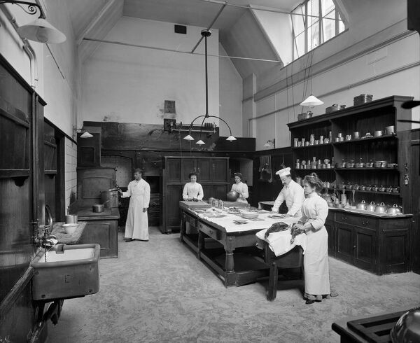 Minley Manor, Hampshire. Staff in the kitchen at a French chateau style country house that was erected between 1858-60 to the designs of architect Henry Clutton