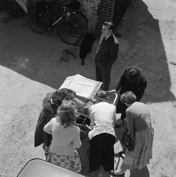 Thaxted, Essex. Looking down at a group of women cooing at a baby in a pram as a man looks on. Photographed by John Gay in the late 1950s
