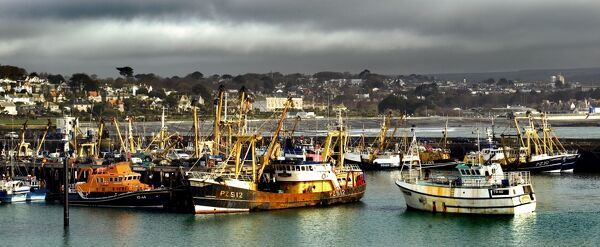 NEWLYN FISHING PORT, Cornwall. Storm clouds settle above the trawlers in the harbour