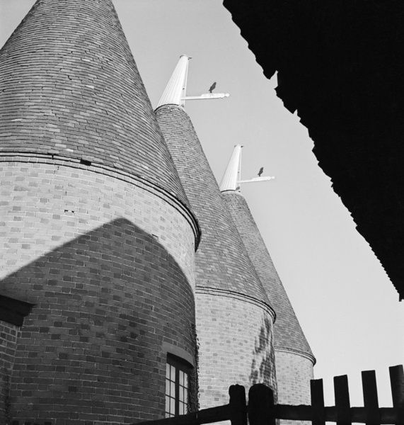 Close-up of three oast houses, viewed from under a roof or awning. Taken in Kent. Photographed by John Gay. Date range: 1955-1959