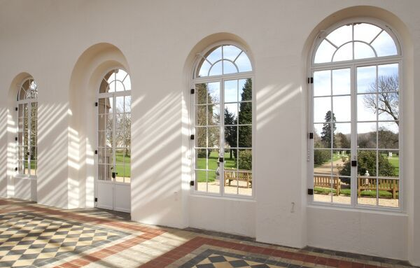 WREST PARK HOUSE AND GARDENS, Bedfordshire. Interior view of the Orangery looking out towards the garden with dappled sunlight filtering through the glass roof