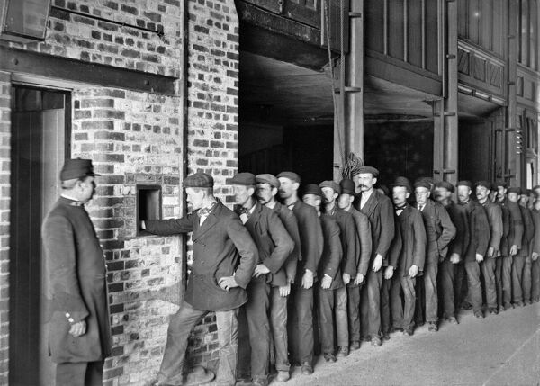 Pay day at Butlers Wharf, Shad Thames, London. A line of workmen collect their wages from a hatch, while a security guard looks on. Photographer unknown, c.1910