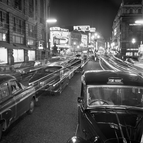 PICCADILLY, London. Stationary traffic along a busy Piccadilly at night, showing a London taxi cab for hire, and the illuminated signs of Piccadilly Circus and Lillywhites in the background. Photographed by John Gay during the 1950's