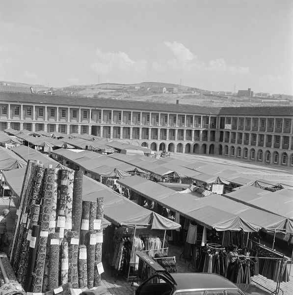 Looking over the market stalls in the courtyard of the Piece Hall in Halifax, West Yorkshire. Originally built as a cloth hall in the late 18th century, the Piece Hall was used as the town's market from 1871. Photographed by John Gay in 1976