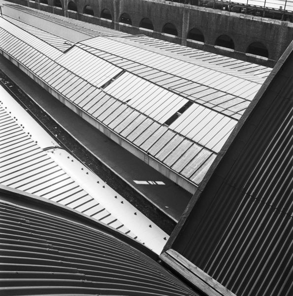 VICTORIA STATION, London. Elevated view looking from the curved, corrugated roof of the train shed down towards the glazed platform canopies at Victoria Station. Photographed by John Gay. Date range: 1960-1972
