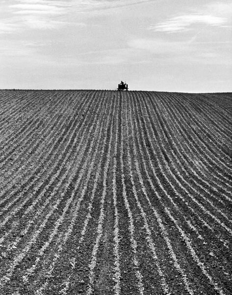 A newly ploughed field near Aylesbury, Buckinghamshire. The farmer on his tractor is sillouhetted on the horizon. Photographed by John Gay during 1950s 1960s