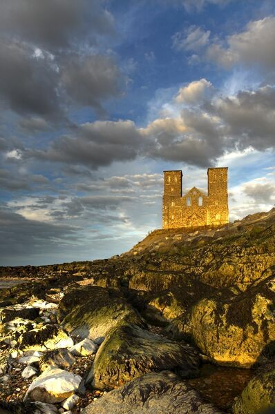 RECULVER TOWERS AND ROMAN FORT, Kent. Twin 12th-century church towers in late afternoon sunshine with scattered clouds