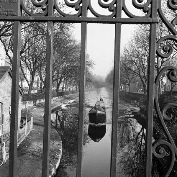 REGENTS CANAL, Little Venice, London. A view north east along Regents Canal in Little Venice, looking through the decorative railings of Warwick Avenue Bridge and showing a barge travelling towards the bridge. Photographed by John Gay. Date range
