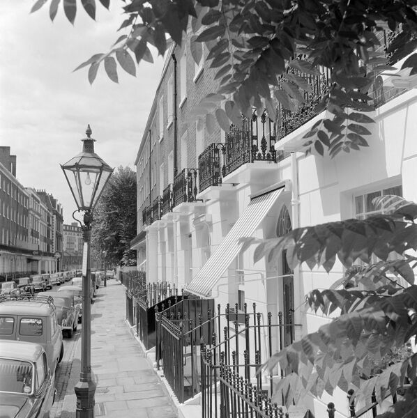 Looking along the pavement of a residential street, probably in the Kensington and Chelsea area of London with 19th century town houses featuring first floor wrought iron balconies and a Victorian lamp standard in the foreground