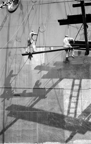 ROYAL ALBERT DOCK, Canning Town, London. Two workmen repainting a ship in dry dock (mid-20th century). The dock was the largest of the three royal docks and opened in 1880.s W Rawlings