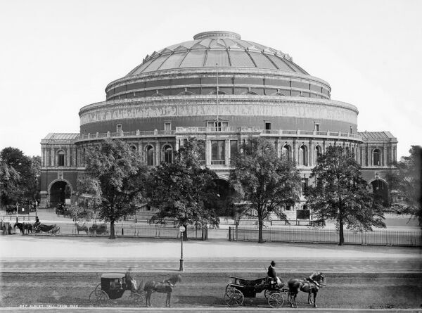 ALBERT HALL, London. A view of the hall from Hyde Park with horse-drawn carriages in the foreground