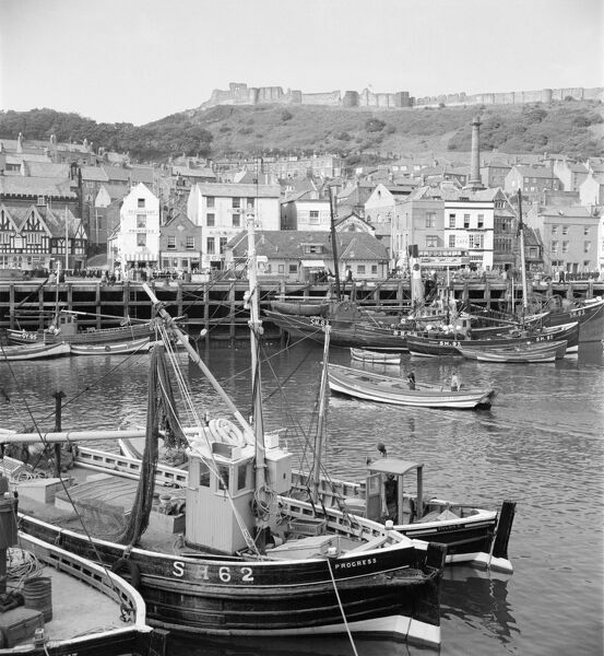 SCARBOROUGH, North Yorkshire. Fishing boats moored in the old harbour, looking towards the town with the castle dominating the hill behind the town. Photographed by Hallam Ashley c.1959
