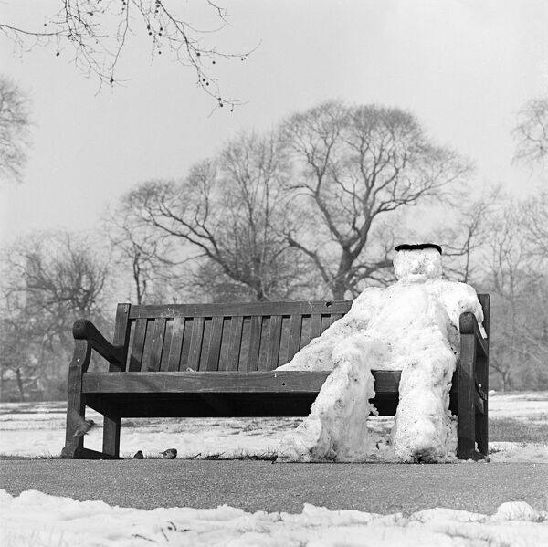 REGENTS PARK, London. A snowman sitting on a park bench. Photograph taken circa 1960 by John Gay