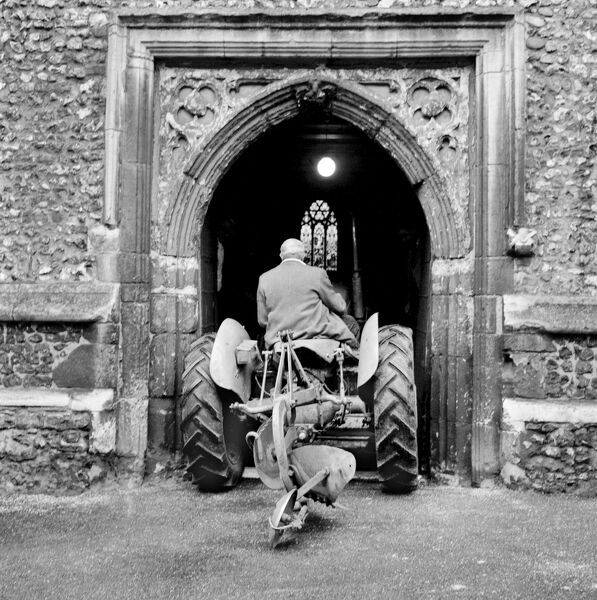 ST ETHELDREDA'S CHURCH, Hatfield, Hertfordshire. View showing a tractor being driven through the 15th century west tower doorway of the church during preparations for the harvest festival in 1960. John Gay