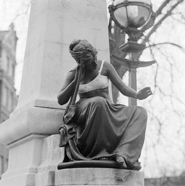 EDWARD ONSLOW FORD MEMORIAL, Abbey Road, St John's Wood, London. The bronze seated female figure on the Edward Onslow Ford memorial, wearing a bra, with obelisk behind and a lamp standard to right. Photographed by John Gay in 1973