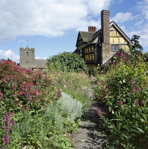 STOKESAY CASTLE, Craven Arms, Shropshire. Exterior view of gatehouse and church with garden in the foreground