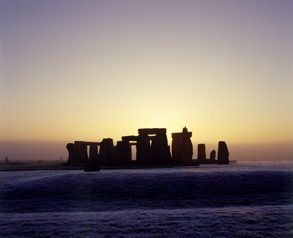 STONEHENGE, Wiltshire. A view from the North West with the stones silhouetted by the rising sun