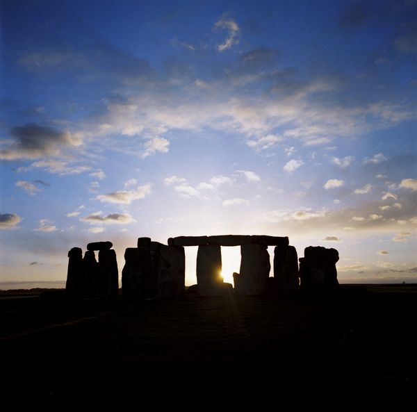 STONEHENGE, Wiltshire. The sun sets behind Stonehenge leaving rich blue sky for all to see