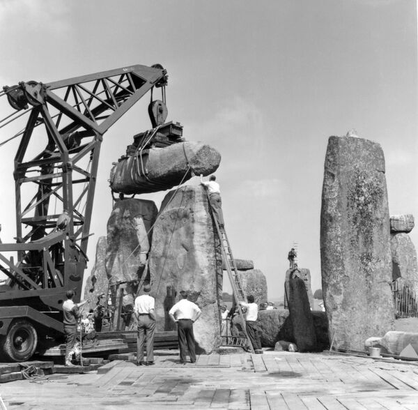 STONEHENGE, Wiltshire. Re-erection of Trilithon lintel 158 by the 60 ton 'Brabazon Crane', the larger of two cranes used to lift stones. The lintel is being lowered and man-handled into its final resting position on upright stones 57 and 58