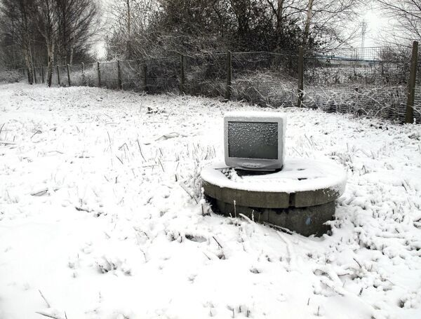 Snow covered computer monitor on a raised manhole