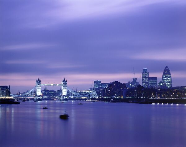 TOWER BRIDGE, London. Tower Bridge and the London skyline at nightfall, with the river Thames in the foreground