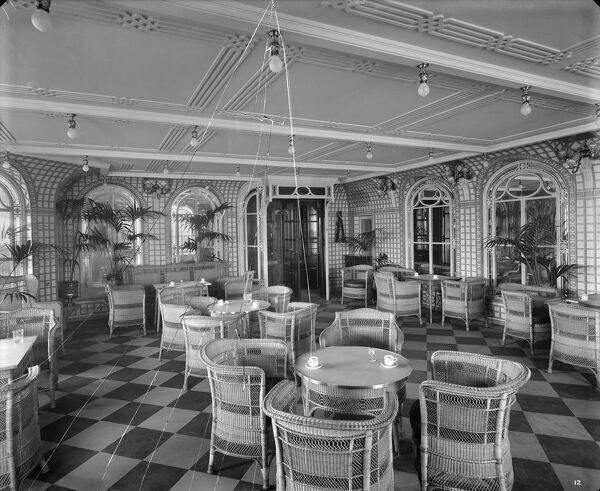 Fractured glass plate negative. Looking forward in the Verandah Cafe, RMS Olympic, White Star Line, 1920-21. The Olympic was sister ship to the ill-fated Titanic and Britannic. This Bedford Lemere and Company photograph was commissioned by the White Star Line