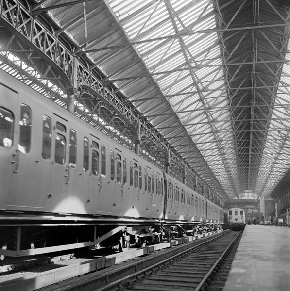 VICTORIA STATION, London. Interior of the station showing two adjoining platforms, one with a train departing, the other with a standing train. Photographed by John Gay. Date range: 1960-1972