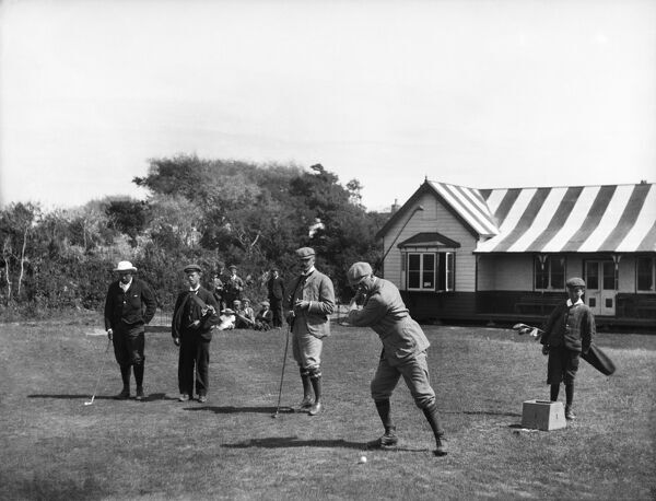 Burnham And Berrow Golf Course, Somerset. Opened in 1891 by Burnham Golf Club, the course was originally nine holes. It was extended in 1896 and the club changed its name to Burnham and Berrow Golf Club. Here golfers prepare to tee off outside the pavilion