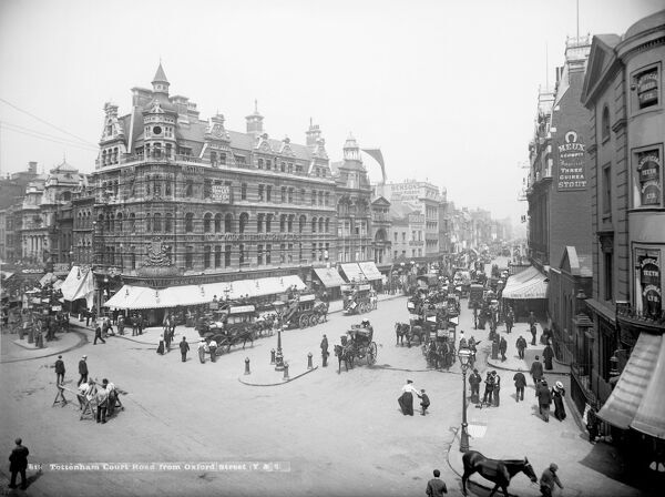 Tottenham Court Road, London. A view looking down a busy Tottenham Court Road from Oxford Street with horse-drawn vehicles and people in the foreground. A large clothing department store lies on the corner where the two roads meet. Photographed by York