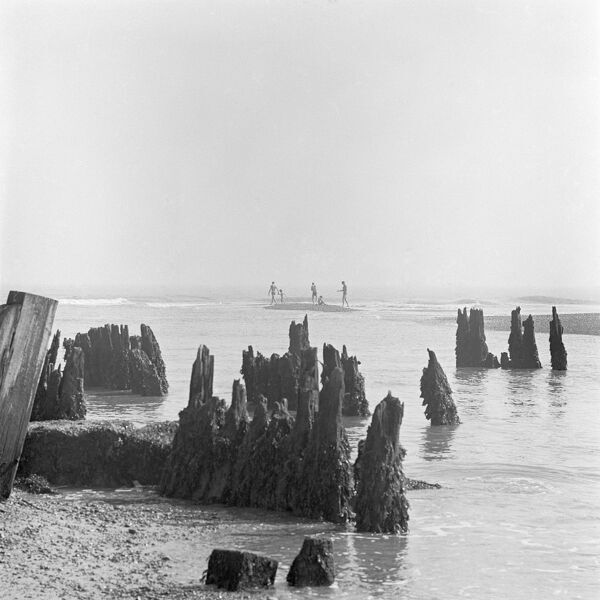 WALBERSWICK BEACH, Suffolk. Rotted wooden posts in the sea at Walberswick, with figures in the distance. Photographed by John Gay in 1969