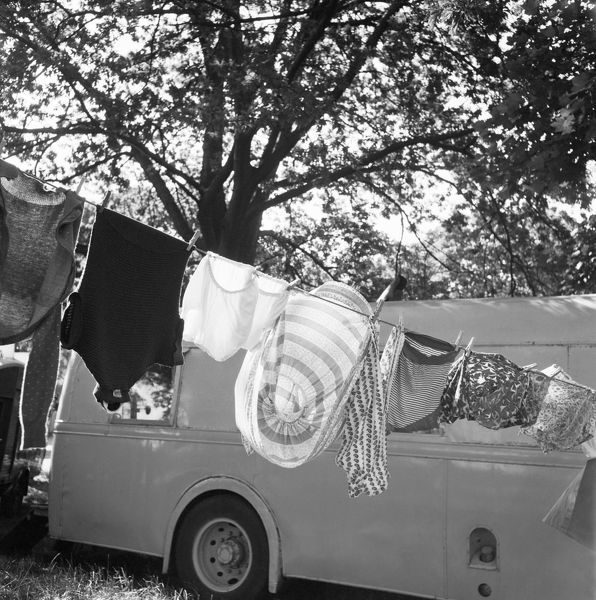 A row of washing hanging on a washing line in front of a caravan parked for the funfair at the Vale of Health, Hampstead Heath. Photographed by John Gay. Date range: 1960 - 1965