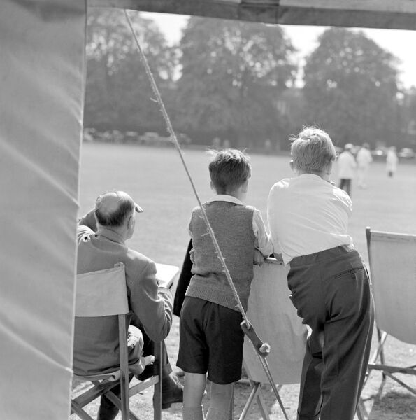 KEW GREEN, London. View of two standing boys and a seated man watching a game of cricket on Kew Green. Photographed by John Gay. Date range: Jan 1962 - May 1964