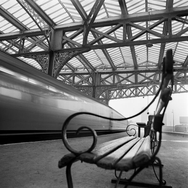 WATERLOO STATION, London. Looking along a bench with curved wrought iron arms on a platform at Waterloo Station with a train passing at speed in the background. Photographed by John Gay. Date range: 1960-1972