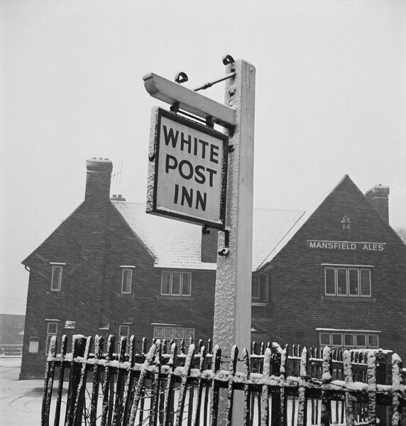 Inn sign for the White Post Inn, in a snow shower. The public house has a Mansfield Ales sign, but the location is uncertain. Photographed by John Gay, 1955-65