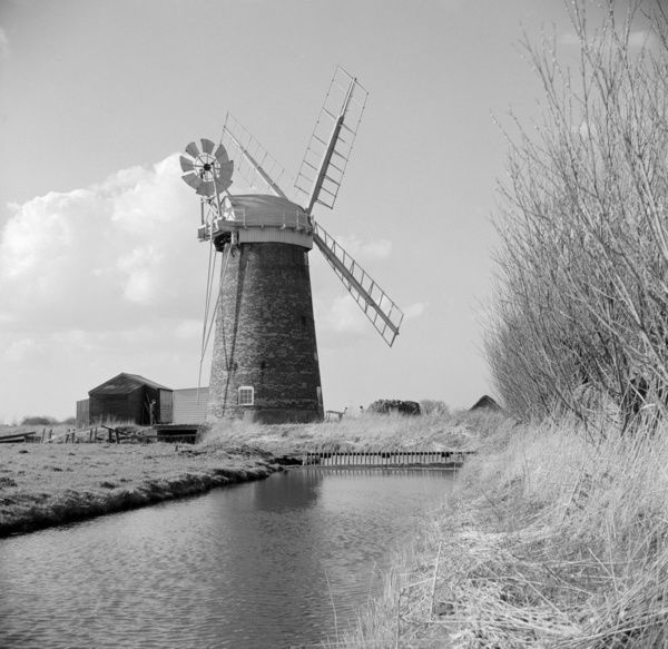 HORSEY STAITHE, Norfolk. This mill was built in 1912 to replace a Victorian one. The shutterless sails power a water-pump, which helps to manage the low-lying Norfolk countryside. Photographed by Hallam Ashley in April 1963