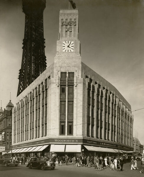 F W Woolworth And Company Limited, Bank Hey Street, Blackpool. Exterior view from the south-west with shoppers on the streets, 1938. Showing the Woolworths Cafe sign on the clock tower and Blackpool Tower in the background